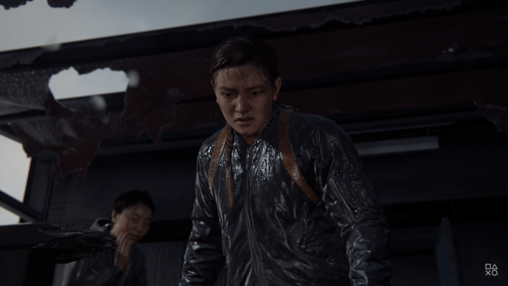 Abby and Lev in The Last of Us Part: II. Lev is in the background whilst Abby looks down, she is wearing a wet rain jacket and looks scared.