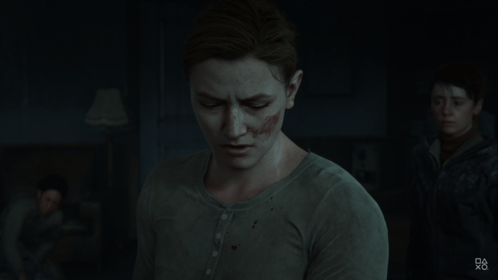 A woman in henley style shirt looks down with blood on her right cheek as people in the packground look on.