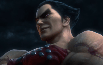 Kazuya from Tekken has arms folded, looking down at the camera, he has red gloves on, red eyes and black slicked back hair. The background is dark grey and cloudy